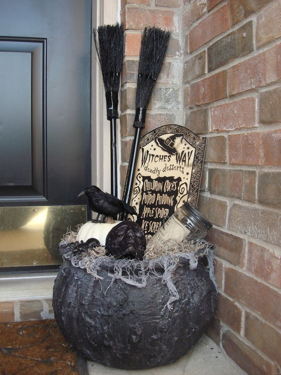 a Halloween porch decoration of an old witch cauldron with a pumpkin, a skull, a jar, a tombstone, a blackbird and some witches' brooms
