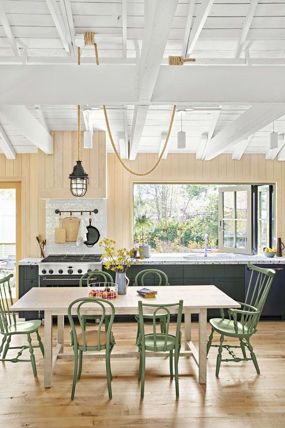 a pretty and charming cottage with warm stained walls and dark cabinetry, a folding pass through window and cool green mismatching chairs