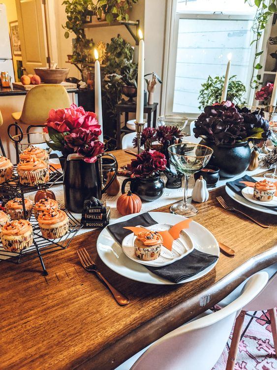 a Halloween tablescape with jugs with dark and bold blooms and a cauldron with dark flowers, candles and delicious cupcakes
