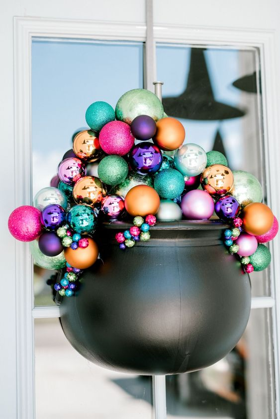 a lovely front door decoration of a cauldron filled with colorful Christmas ornaments is a gorgeous alternative to a usual Halloween wreath