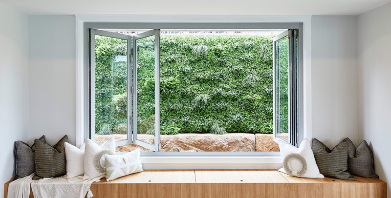 a folding window with a built in storage daybed with lots of pillows and a greenery view is a gorgeous idea for a modern space