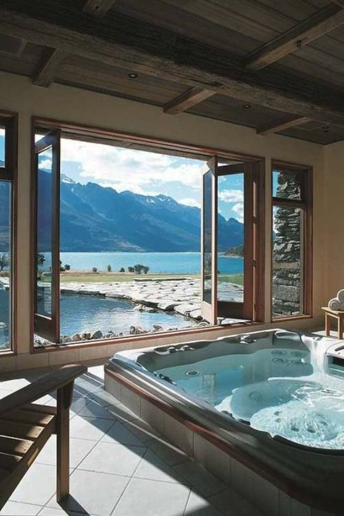 a gorgeous spa bathroom is opened to outdoors with a folding window that allows making this bathroom indoor outdoor at once