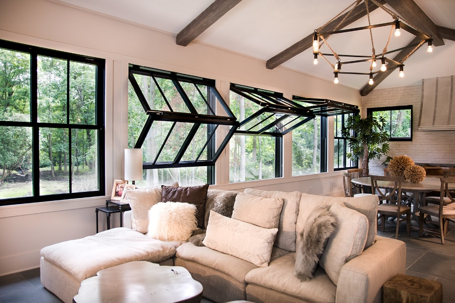 a neutral living room with a cool bulb chandelier and black folding up windows that easily open up the space to outdoors