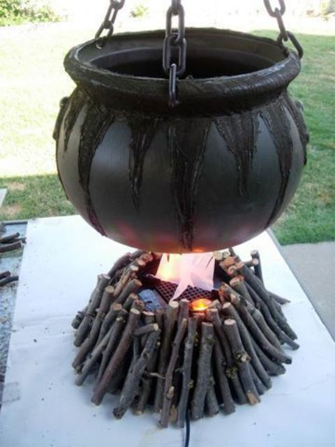 an outdoor Halloween decoration of a witch cauldron with branches under it and some candles is an easy decoration to go for