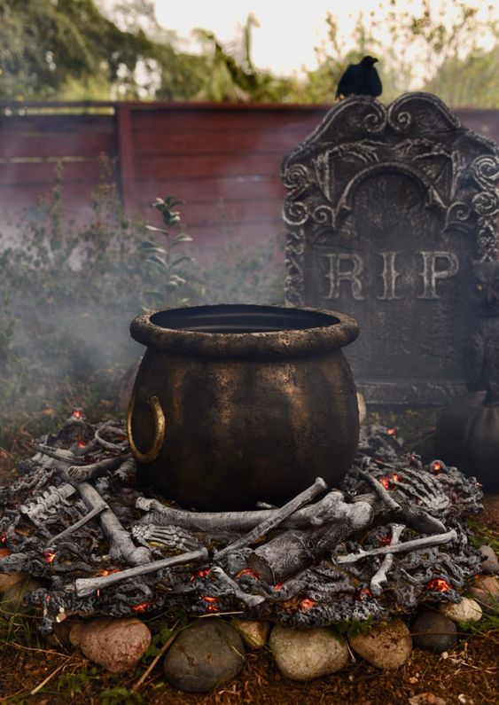 a realistic witches' cauldron with faux bones under it and a tombstone for cool and bold Halloween decor that can be realized fast