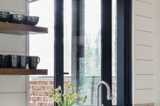 25 a white farmhouse kitchen with a black folding window, black sconces and thick open shelves with black tableware