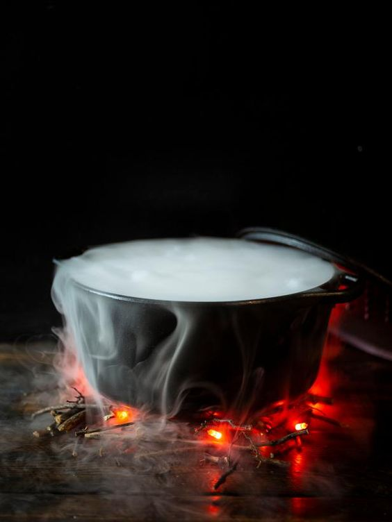 a simple and modern Halloween decoration of a cauldron with smoke and branches and lights that imitate fire is cool