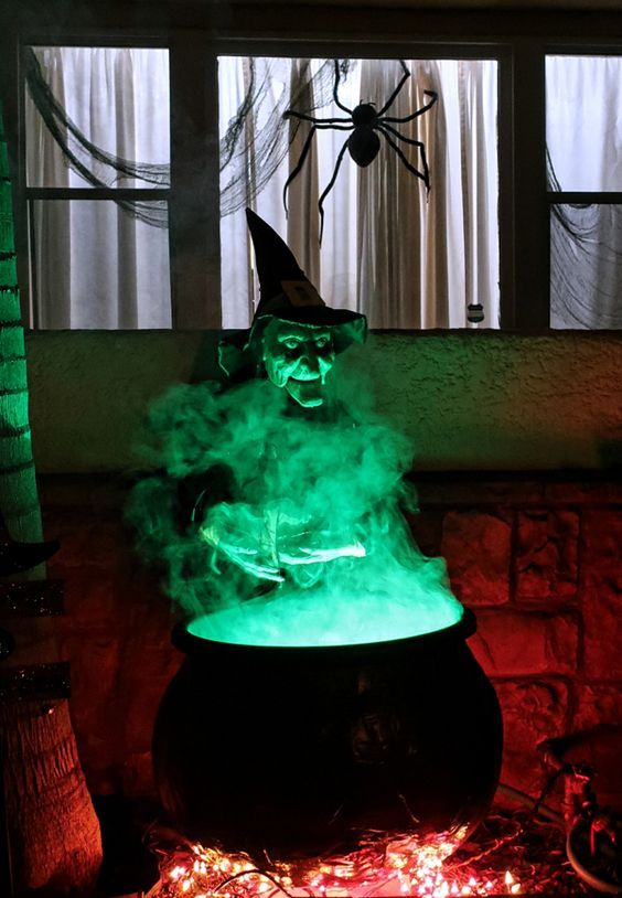 a witch cauldron prop wih additional green lights and some lights under it is a cool solution for outdoor Halloween decor