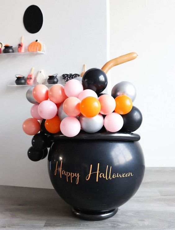 a witches' cauldron filled with colorful balloons is a fun and cool idea to rock at Halloween, will do for both adults' and kids' parties
