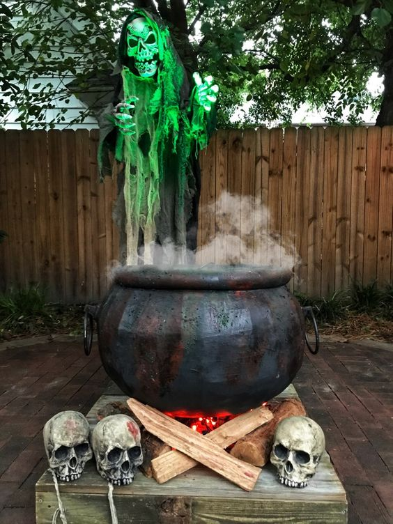an outdoor Halloween decoration of a realistic cauldron, firewood and lights, skulls and some smoke is amazing
