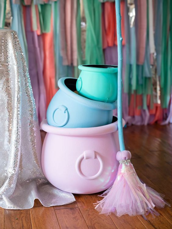 pastel-colored cauldrons and a broom fro styling a fun adult or a sweet kids' Halloween party