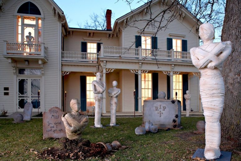 a Halloween yard with a number of mummies, tombstones, planters and spiders is perfect for Halloween