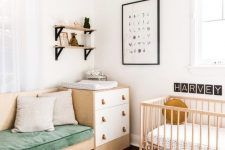 a Nordic chic nursery with white and stained furniture, a built-in sofa, a brigth striped rug, open shelves and a printed pouf