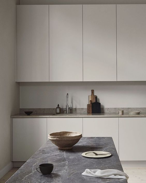a Nordic greige kitchen with sleek cabinets, a neutral stone countertop, a grey stone table and pretty tableware