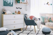 a Scandi nursery with bright touches – artworks, pillows, a pouf and a chair and some bright bedding in the crib is lovely