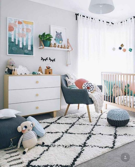 a Scandi nursery with bright touches   artworks, pillows, a pouf and a chair and some bright bedding in the crib is lovely