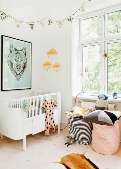 a Scandinavian nursery with a white crib, a green artwork, printed bunting, printed baskets with pillows and toys and a mobile