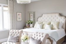 a beautiful and sophisticated greige bedroom with creamy upholstered furniture, neutral pillows, pritned curtains and a rug, a pendant lamp with crystals and mirrors