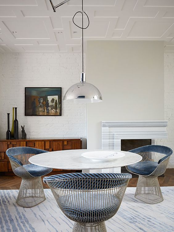 a beautiful eclectic dining room with white brick walls, a greige touch, a fireplace, a round table, blue chairs, a shiny pendant lamp and vases
