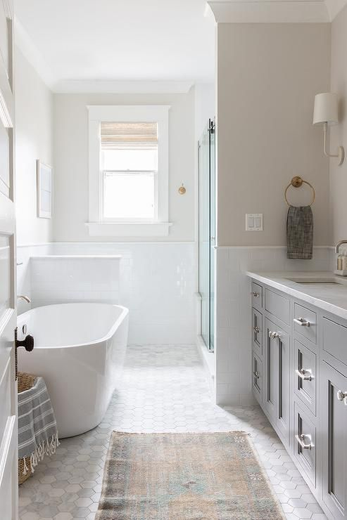 a beautiful farmhouse bathroom with greige walls and a marble hex tile floor, a grey vanity and an oval tub, a shower space