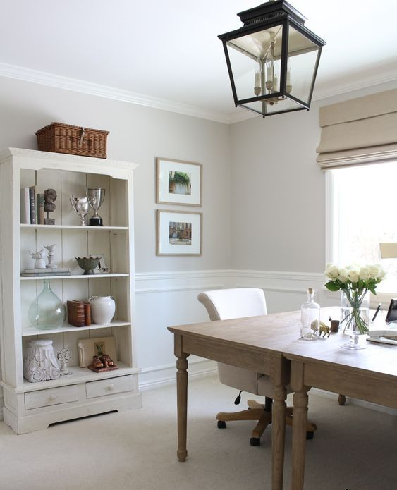 a beautiful farmhouse home office with greige walls and white panels, a neutral planked storage unit, stained tables and a pendant lantern