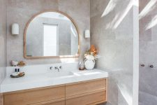 a beautiful greige bathroom clad with large scale tiles, a light-stained built-in vanity, an arched mirror and a dried leaf arrangement