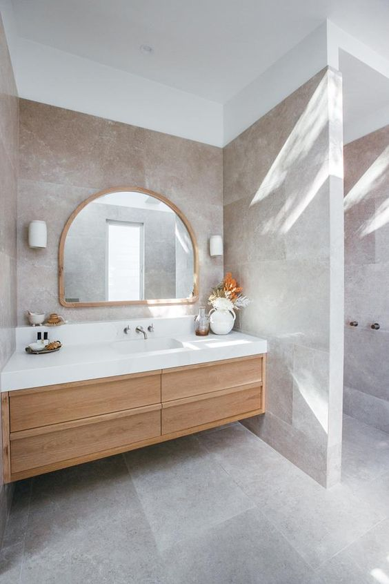 a beautiful greige bathroom clad with large scale tiles, a light stained built in vanity, an arched mirror and a dried leaf arrangement