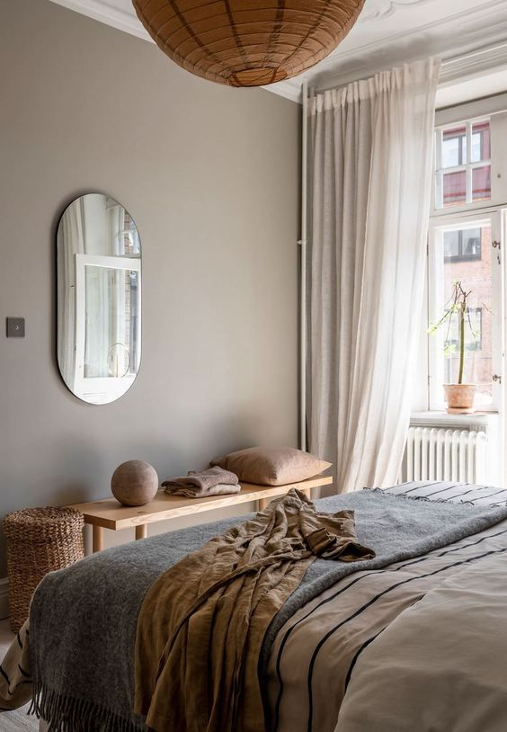a beautiful greige bedroom with a bed with neutral and printed bedding, a wooden bench, warm colored textiles, a paper pendant lamp and a basket for storage