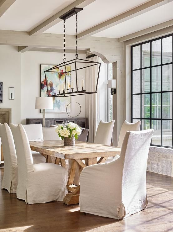 a beautiful vintage farmhouse dining room with neutral walls and greige wooden beams, a wooden dining table, upholstered chairs and a chandelier
