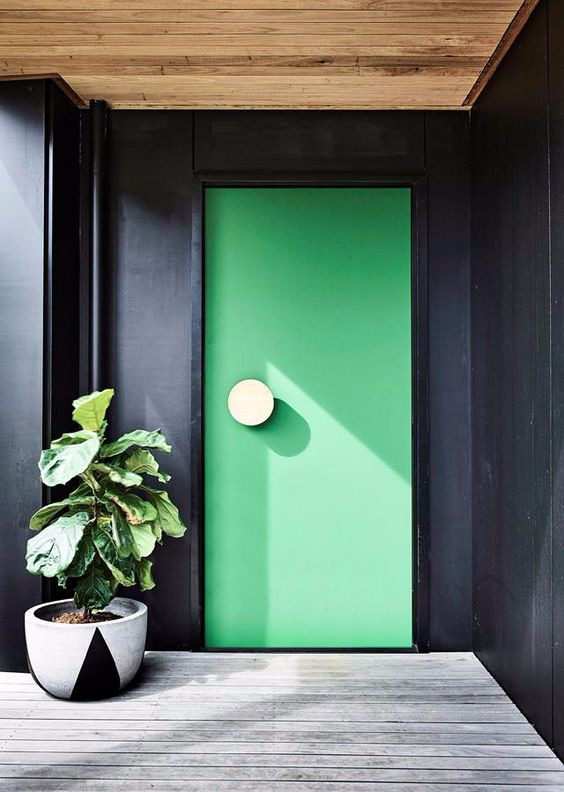 a black entrance with a whitewashed deck and an apple green front door accented with a large round white knob