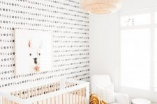 a boho Scandi nursery with lunar wallpaper, a neutral crib, a rocker, a coffee table and a jute pouf plus a pendant lamp