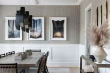 a bold and whimsy greige dining room with white paneling, a wooden table, woven chairs, black pendant lamps, a glass console table and gallery walls
