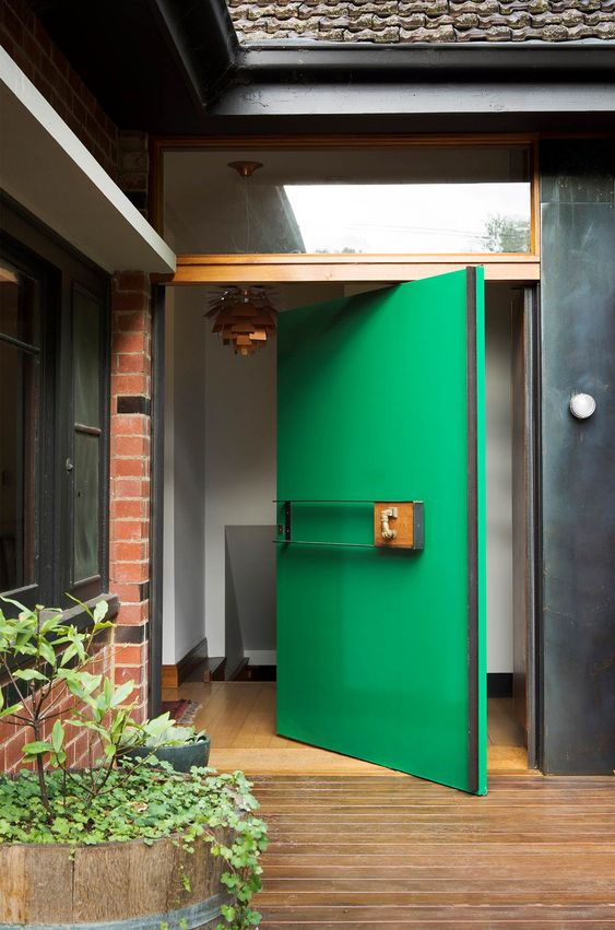 a bold green oversized aquare pivot front door is a creative solution for a modern home, it will make a statement both with its color and design