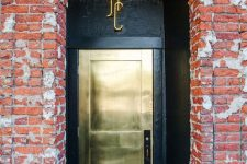 a brass finish metal front door plus a black entry make a bold and contrasting statement and make the entrace very dramatic