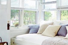 a bright and fresh windowsill reading nook with a built-in daybed with pillows and a shabby chic table