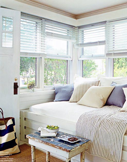 a bright and fresh windowsill reading nook with a built in daybed with pillows and a shabby chic table