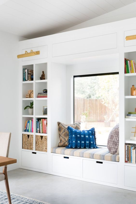 a bright contemporary reading nook with an upholstered bench, drawers and built in shelves