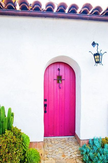 a bright pink arched wooden door with a small window and a black handle is a fantastic solution for a mansion or a French or Spanish country house