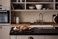 a catchy greige kitchen with shaker cabinets, black and butcherblock countertops, an open storage cabinet, modern appliances and vintage fixtures