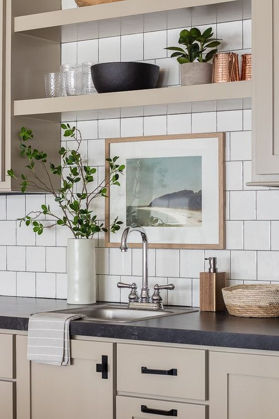 a catchy greige kitchen with shaker cabinets, built in shelves, black handles, a white square tile backsplash and black stone countertops