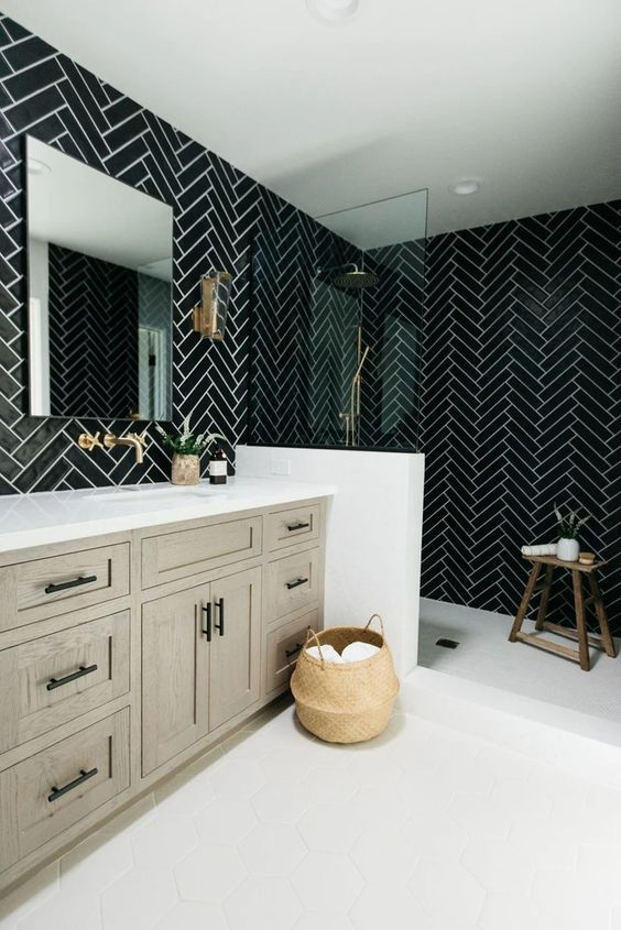 a chic black and white bathroom with chevron tiles, a greige wooden vanity, black fixtures and a wooden stool plus a basket for storage is cool