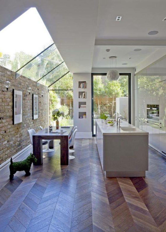 a chic contemporary space with a sleek white kitchen and a dining space lit up with a large window that flows into a large skylight