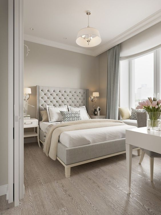 a chic greige bedroom with a grey upholstered bed, neutral bedding, a white vanity and a grey chair, blue curtains and some elegant lamps
