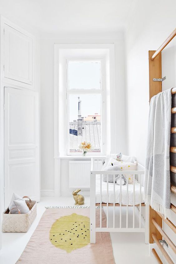 a chic neutral Scandi nursery with white furniture, pastel pillows and a rug, a basket for storage is a small and cute space