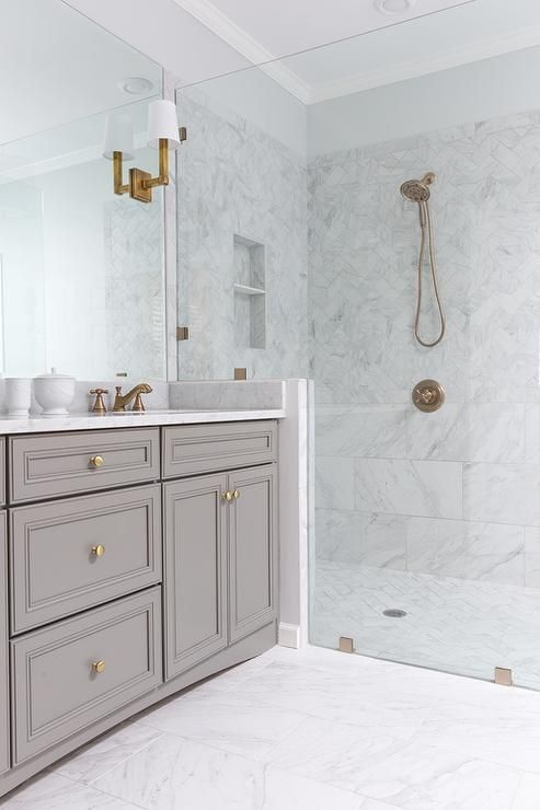 a chic white bathroom clad with marble tiles, with a greige vanity, brass and gold fixtures and a large mirror that takes a whole wall