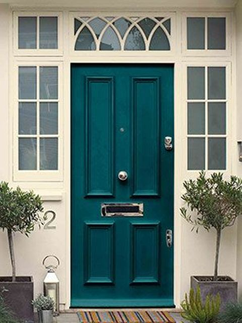 a classic front door with French sidelights painted teal looks bold and unusual and makes a statement with its color at once