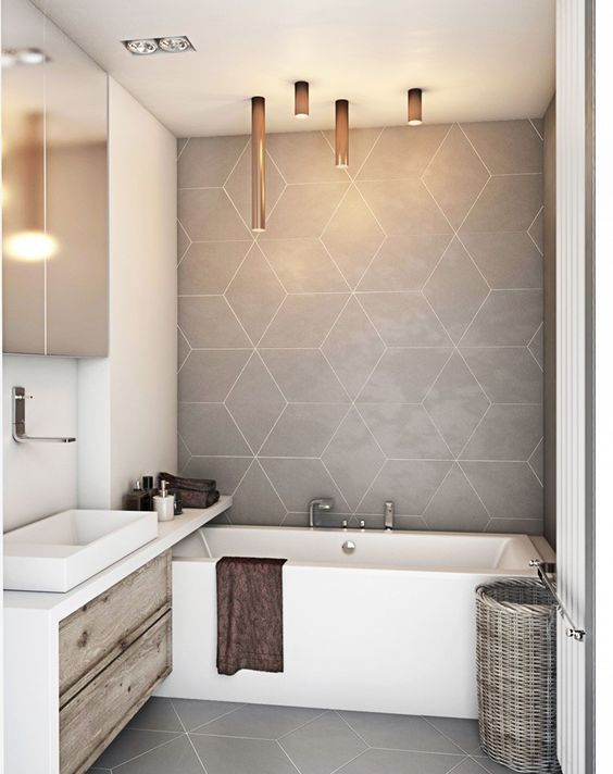 a contemporary bathroom with greige geo tiles and a floor, a built in vanity, a built in tub a mirror cabinet and tube lighting