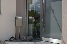 a contemporary entrnace with a grey metal front door with an oversized handle and a window on the left is a cool idea