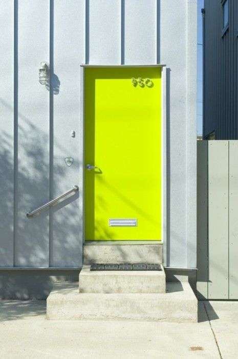 a contemporary front door painted neon yellow and with a house number is ultimate idea to make a bold statement with color