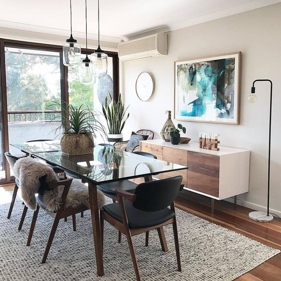 a cool modern greige dining room with a stylish credenza, a glass table and black chairs, pendant bulbs, potted plants and a floor lamp